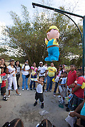 Parque del Este. Kids trying to punch a hole into a Pin?ata, a puppet filled with sweets. This is usually done to celebrate one of the kids' birthday.