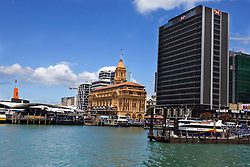 Ferries are docked along various piers near the Ferry Building in the central business district of Auckland, New Zealand