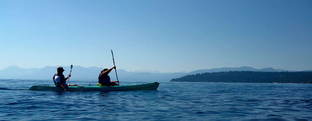 travel, recreation, outdoor sports: a heterosexual man and woman married couple kayaks together on the blue waters of lake tahoe, central california, usa