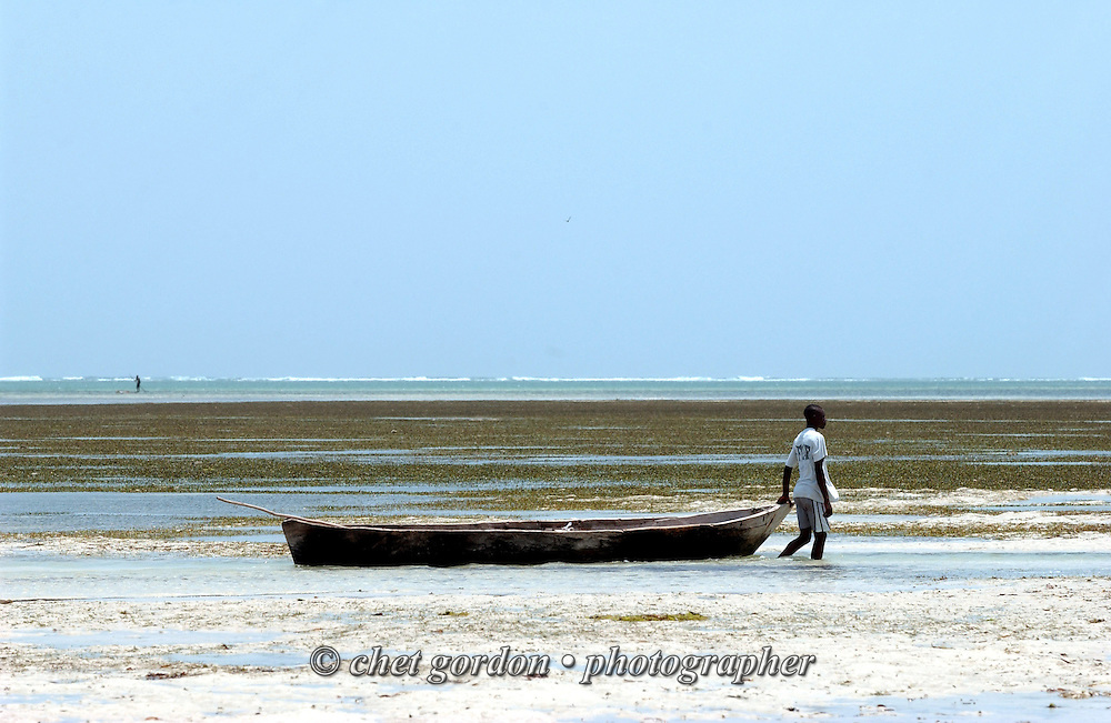 A fisherman steadies his dhow in the surf during low tide at Bamburi Beach in Mombasa, Kenya on Friday, February 6, 2004.