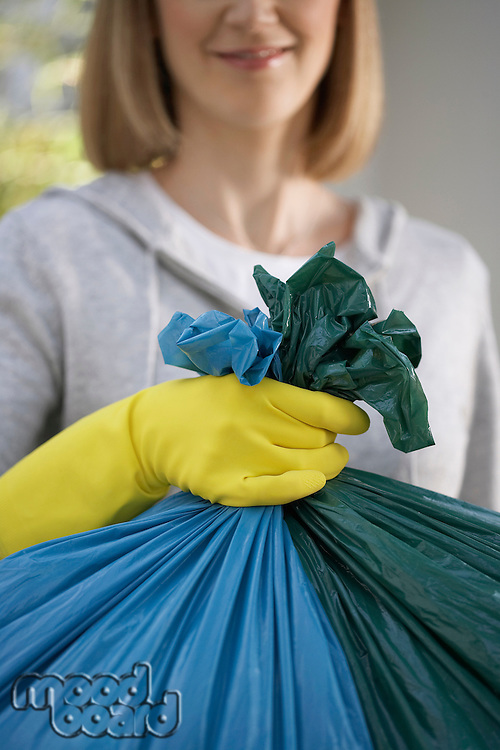 Woman wearing rubber gloves holding garbage bag close-up