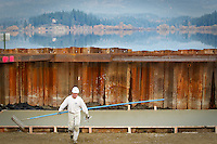 Mitch Whetzel, with Mitch Whetzel Concrete, carries equipment up the grade of the Hauser Lake boat launch Friday after smoothing a freshly pour concrete slab.