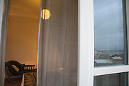 """One of the rooms of hotel """"Casa das janelas com Vista"""", with 25th of April bridge reflected on the window."""