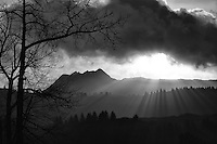 Fingers of sunlight stream through clouds, mountains and trees on Kodiak Island