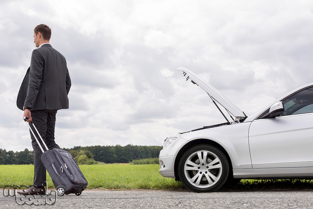 Full length rear view of young businessman with luggage leaving broken down car at countryside