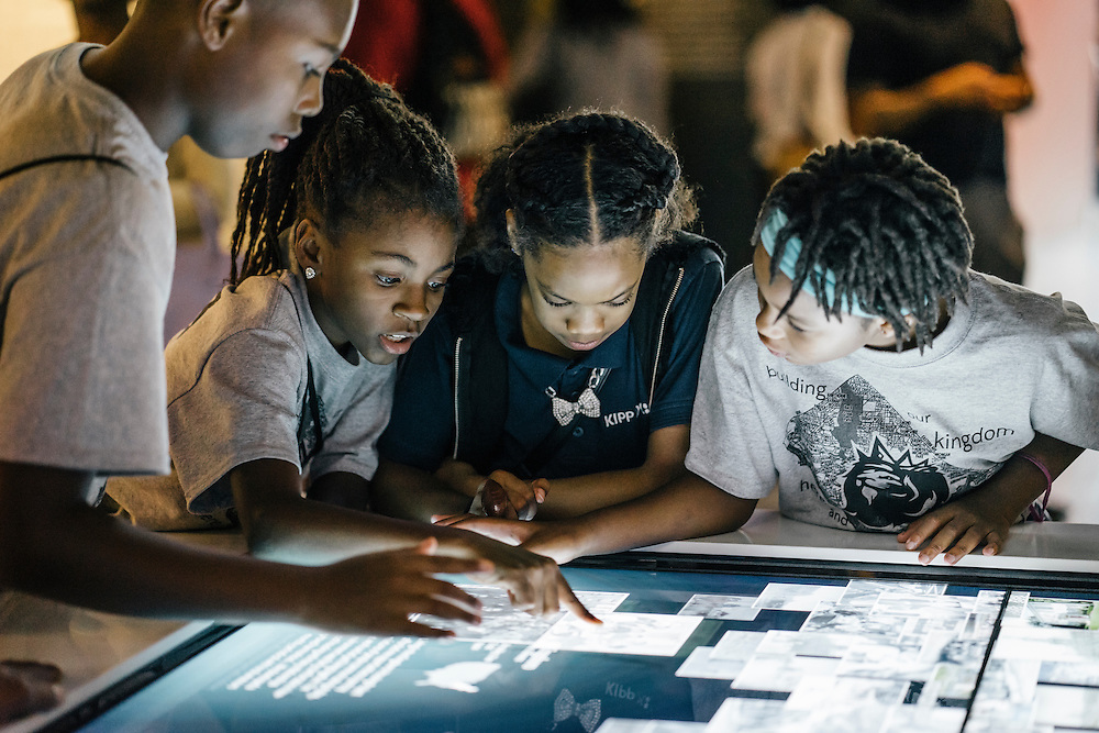 Sixth-graders from Knowledge Is Power Program (KIPP) DC, including Kalicko Smith, 12, left, Imani Poston, 11, left center, Michaela Young, 11, right center, and Makayla Hall, 11, right, use an interactive display with historic photos inside the Smithsonian National Musuem of African American History and Culture during their visit on Oct 21, 2016. The students spent an hour touring the new Washington, D.C. museum, which is only available to see with reserved tickets during the first year.