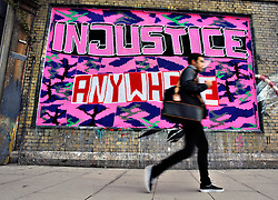 "© Licensed to London News Pictures. 02/10/2012. London,UK.People walks in front of a graffiti ""Injustice Anywhere Is A Threat To Justice Everywhere"" on Great Eastern Street today 2 October 2012 .Photo credit : Thomas Campean/LNP."