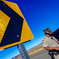 A traffic sign points the way to Ramah Navajo Police Officer Deirryck Clichee as he prepares a speed warning  during a traffic citation stop in Mountain View Monday.