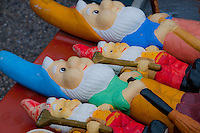 A colorful line of vintage garden gnomes for sale on a red table.