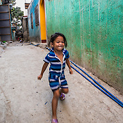 CAPTION: As Angel plays in the lane, she is blissfully unaware of how this thoroughfare could become inundated by foul water during future floods. Inadequate drainage and the build-up of waste are two of the problems contributing to flooding in Marikina. The local government has banned plastic and polystyrene in the city, and local businesses are adhering to this rule. Hilda says she thinks it's helping to reduce the impact of flooding. LOCATION: Ampalaya Street, Barangay Tumana, Marikina City, Philippines. INDIVIDUAL(S) PHOTOGRAPHED: Angel Lu Santos.