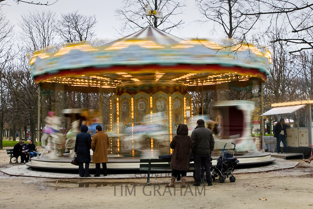 Parents watch their children on the carousel in Jardin des Tuileries, Central Paris, France
