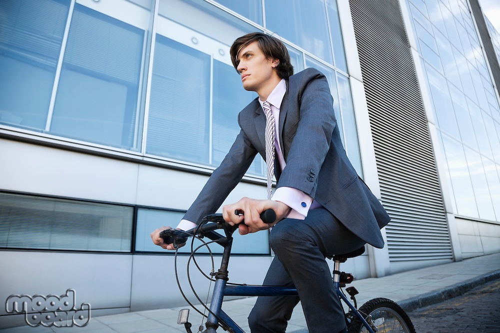 Low angle view of young businessman riding bicycle by building