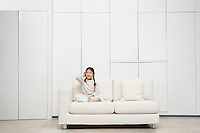 Young barefoot Girl sitting cross-legged Sofa