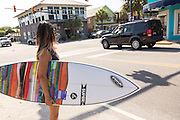 A young woman surfer waits to cross the road in Folly Beach, SC.