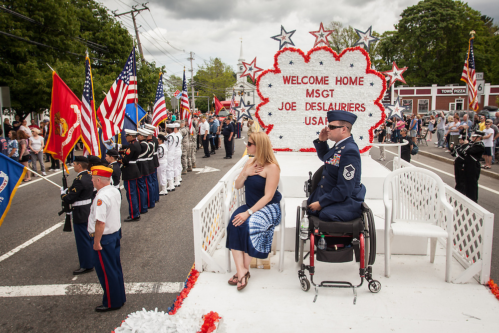 Injured Air Force Master Sgt. Joseph Deslauriers Jr. sits on a parade float with his wife Lisa during a Memorial Day parade where he served as grand marshall in his home town of Bellingham, MA on Sunday, May 19, 2013. The parade was held a week before the holiday to ensure greater attendance. In 2011, Deslauriers lost both of his legs and part of an arm after stepping on an explosive device while stationed in Afghanistan. He is currently rehabbing at Walter Reed Army Medical Center.  (Matthew Cavanaugh for The Washington Post)