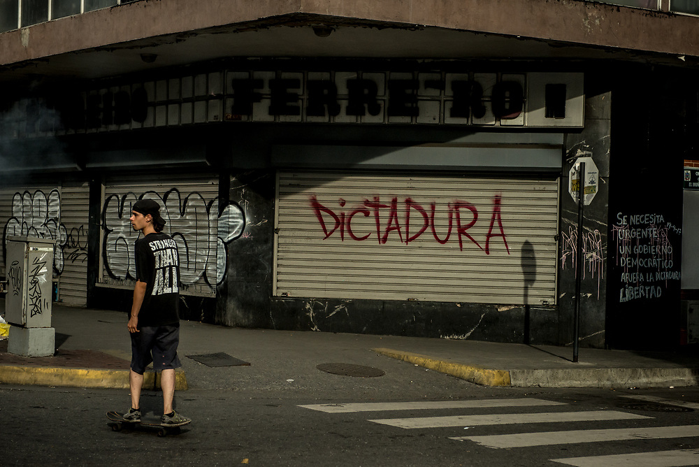 "CARACAS, VENEZUELA - JULY 27, 2017: A young man skateboards past a shop closed in support of a national strike, with graffiti on the security door that says, in Spanish: ""Dictatorship"". The political opposition called for a 48 hour national strike for July 26th and 27th, and for their supporters to close businesses, not go to work, and instead create barricades to block off their streets.  Opposition controlled areas of the country were completely shut down.  The strike was called as part of the opposition's civil resistance movement - that began on April 1st, to protest against the Socialist government's attempt to elect a new constituent assembly that will have the power to re-write the constitution, and will threaten democracy.  PHOTO: Meridith Kohut for The New York Times"