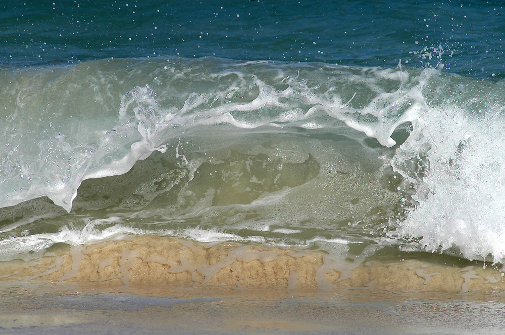 Small beach wave on the sand