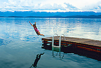 Girl jumping into Flathead Lake at Lakeside, Montana USA
