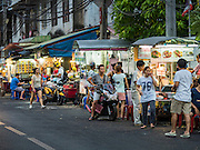 26 MAY 2015 - BANGKOK, THAILAND:  People walk past street food stalls on Sukhumvit Soi 38 in Bangkok, one of the most famous street food locations in the Thai capital. The food carts and small restaurants along the street have been popular with tourists and Thais alike for more than 40 years. The family that owns the land along the soi recently decided to sell to a condominium developer and not renew the restaurant owners' leases. More than 40 restaurants and food carts will have to close. The first wave of closings could start as soon June 21 and all of the restaurants are supposed to close over the next several months.    PHOTO BY JACK KURTZ