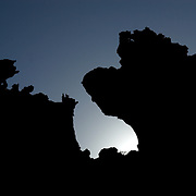 Oman, Ra's al-Jinz. March/14/2008...Rock formations along Ra's al-Jinz's craggy coast-line silhouetted against a setting sun.