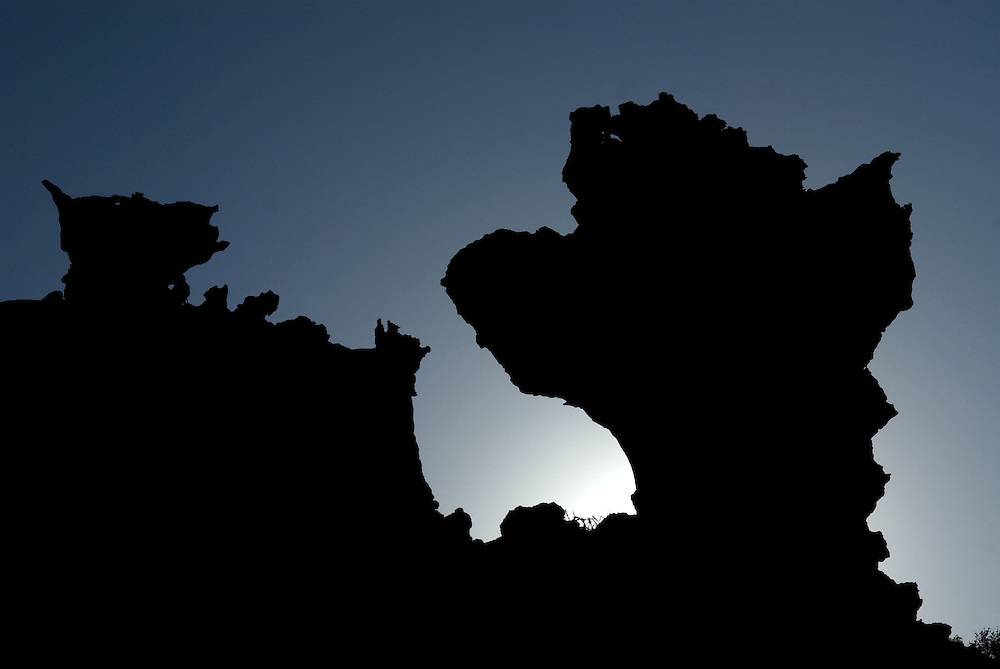 Oman, Ra's al-Jinz. March/14/2008...Rock formations along Ra's al-Jinz's craggy coast-line silhouetted against a setting sun.