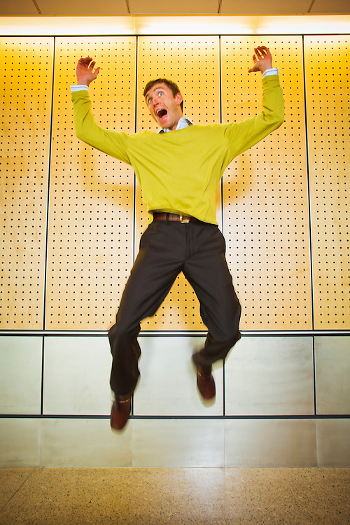 An excited young businessman jumping in the air.