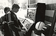teenage boys playing slot machine at automat Holland