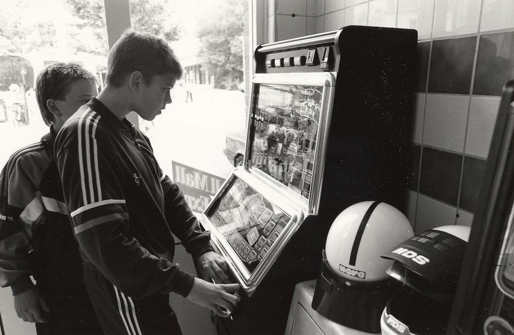 teenage boys playing slot machine at automat Holland