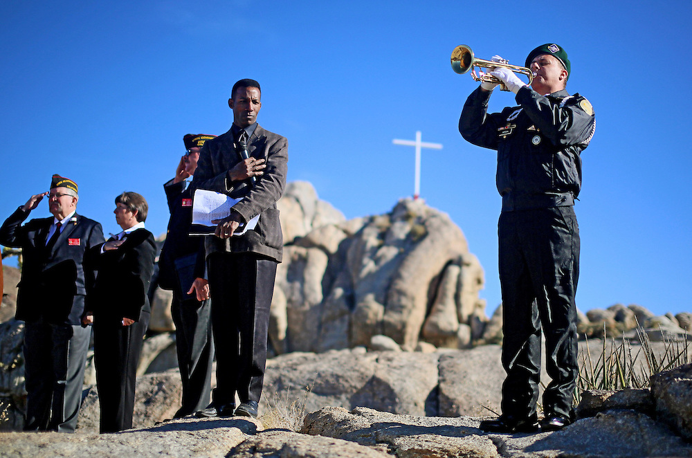 A military bugler plays TAPS during an unveiling ceremony for the Mojave Cross on Veterans Day in Cima, California on Sunday, November 11, 2012.  A battle has been brewing for over Thirteen years over whether the cross can legally stay on Sunrise Rock because it violates Separation of Church and State and is in the Mojave National Perserve which is on Federal Lands.  The Veterans of Foreign Wars and American Legion Society raised money to purchase the plot of land and has kept the cross in place and today serves as war memorial.(Photo by Sandy Huffaker)