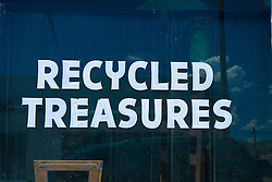 "sign on a storefront window, ""recycled treasures"""