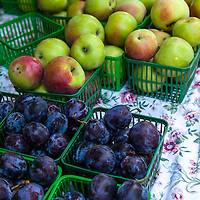 Baskets of large dark purple plums and green apples at a farmers market.