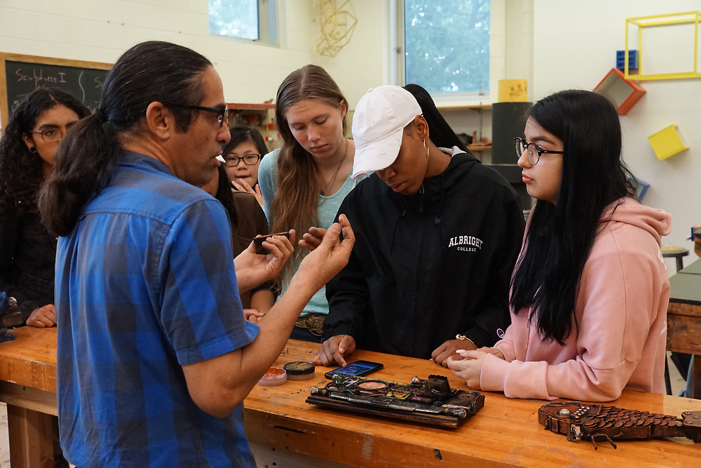 Cuban artist-in-residence at GoggleWorks Center for the arts, demonstrates found object collage to Albright College students.