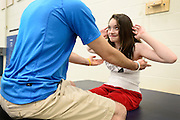 Riley Ljungdahl, 12, of Longmont, smiles as she maintains her balance while Clinical Exercise Specialist TC Doyle tries to destabilize her during physical therapy, Tuesday, April 30, 2013, at the Peak Center at Craig Hospital.<br /> (Matthew Jonas/Times-Call)