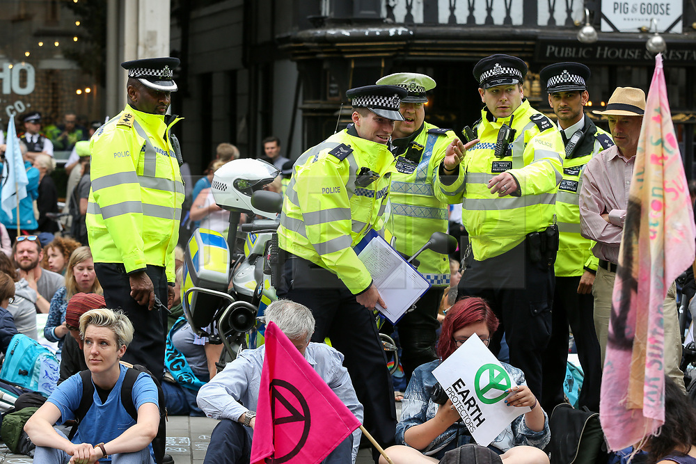 © Licensed to London News Pictures. 15/07/2019. London, UK. Large police presence as hundreds of Extinction Rebellion climate change activists protest outside the Royal Courts of Justice demanding the legal system take responsibility in the climate change crisis, and ensure the safety of future generations by making ecocide law. The environmental group is staging similar protests in Leeds, Cardiff, Glasgow, Bristol, Norwich and other cities around the country. Photo credit: Dinendra Haria/LNP