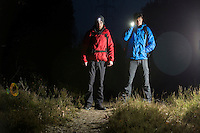 Full length portrait of male hikers with flashlights in field at night