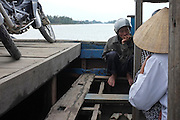 © Licensed to London News Pictures. 04/01/2012. A man rests with his moped on a ferry crossing from Hoi An to Cam Kim Island on the Thu Bon River, Vietnam. Photo credit : Stephen Simpson/LNP