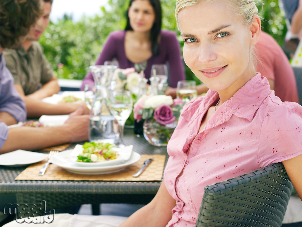 Young woman sitting with friends around patio table socialising eating and drinking