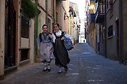 Two young girls dressed up as traditional basque women in the streets of Getaria.