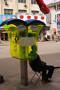 A man sits on a chair in a florescent yellow telephone booth. Pingyao, People's Republic of China