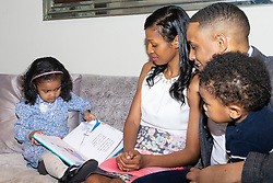Four-year-old Alannah George cuddles reads to her Mum Nadine, Dad XXX and little brother XXX. Alnnah has an IQ of 140 and taught herself to read at two-and-a-half and is a member of Mensa. Iver, Buckinghamshire, March 10 2019.