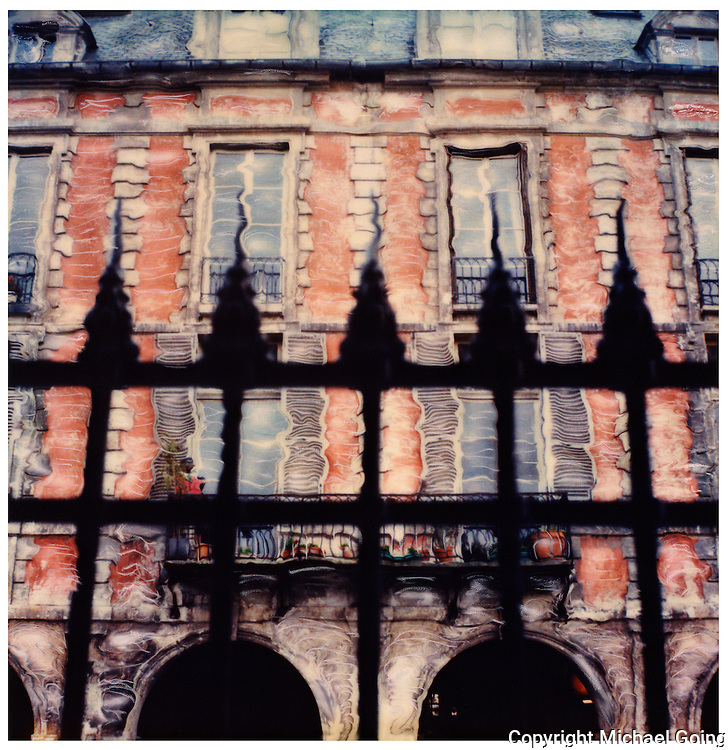 Altered Polaroid of spiked iron fence against red brick apartments Place des Vosges, Paris