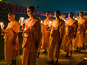 "22 FEBRUARY 2016 - KHLONG LUANG, PATHUM THANI, THAILAND: Buddhist monks participate in the candle light procession around the chedi during the Makha Bucha Day service at Wat Phra Dhammakaya.  Makha Bucha Day is a public holiday in Cambodia, Laos, Myanmar and Thailand. Many people go to the temple to perform merit-making activities on Makha Bucha Day, which marks four important events in Buddhism: 1,250 disciples came to see the Buddha without being summoned, all of them were Arhantas, Enlightened Ones, and all were ordained by the Buddha himself. The Buddha gave those Arhantas the principles of Buddhism, called ""The ovadhapatimokha"". Those principles are:  1) To cease from all evil, 2) To do what is good, 3) To cleanse one's mind. The Buddha delivered an important sermon on that day which laid down the principles of the Buddhist teachings. In Thailand, this teaching has been dubbed the ""Heart of Buddhism."" Wat Phra Dhammakaya is the center of the Dhammakaya Movement, a Buddhist sect founded in the 1970s and led by Phra Dhammachayo.      PHOTO BY JACK KURTZ"