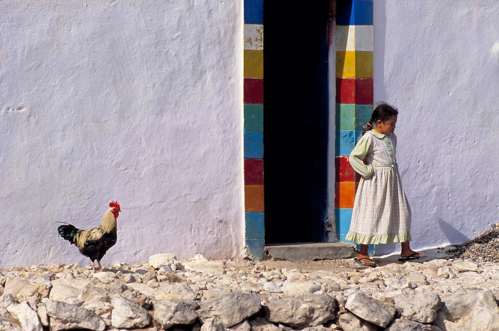A young maroccan girl and a cockerel stand next to a  colourful doorway in Cap Sim, Marocco