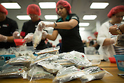 "Sealed bags of food containing rice, soy, and vegetables are packaged by more than 300 SanDisk employees work together to pack food during the Stop Hunger Now Foundation's ""Mayday, Mayday"" food-packing event at SanDisk Corporation in Milpitas, California, on May 13, 2014. (Stan Olszewski/SOSKIphoto)"