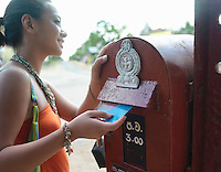 Young woman putting postcard to mailbox smiling