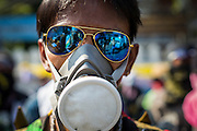"01 DECEMBER 2013 - BANGKOK, THAILAND: An anti-government protestor with his ""gas mask"" and ""goggles."" Thousands of anti-government Thais confronted riot police at Phanitchayakan Intersection, where Rama I and Phitsanoluk Roads intersect, next to Government House (the office of the Prime Minister). Protestors threw rocks, cherry bombs, small explosives and Molotov cocktails at police who responded with waves of tear gas and chemical dispersal weapons. At least four people were killed at a university in suburban Bangkok when gangs of pro-government and anti-government demonstrators clashed. This is the most serious political violence in Thailand since 2010.    PHOTO BY JACK KURTZ"