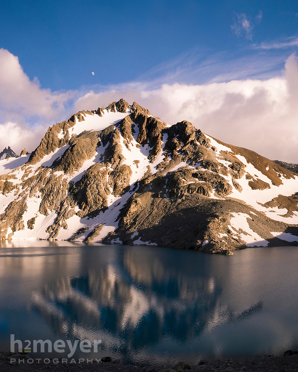 A brief respite from the incessant Patagonian wind allowed for a view of the moon and a partial reflection of Cerro Madsen on Laguna de los Tres at sunrise.   Laguna de los Tres was named for the original party of 3 to successfully summit Mount FitzRoy which lies to the west of the glacier fed lake.  The Andean peak is located in a disputed border region between Chile and Argentina, but most commonly accessed via the town of El Chalten and the Parque Nacional Los Glaciares on the Argentine side.  Image is a stitched composite.