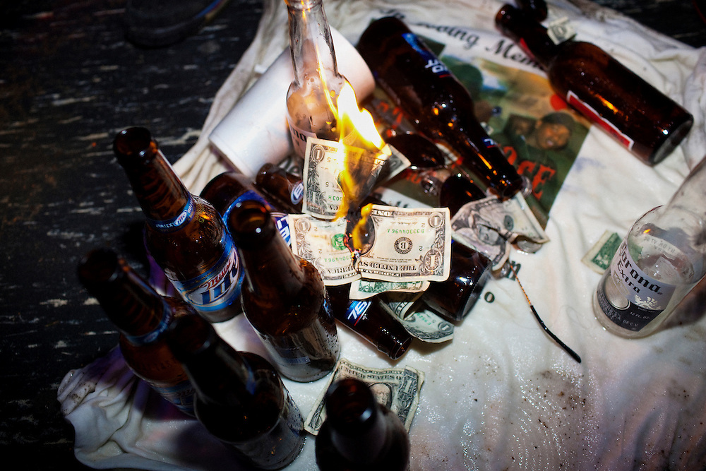 "A flame burns on top of a pile of scattered money, beer bottles and the t-shirt commemorating the life and death Demetrius ""Butta"" Anderson, 18, the night after his funeral in the  Baptist Town neighborhood of Greenwood, Mississippi on Friday, November 5, 2010. After the funeral and burial a block party ensued, where the town residents celebrated Butta's life. Late that night many of his friends and some family gathered at Scruples, a club down the highway in Itta Bena, Mississippi and danced and drank until the bar closed."