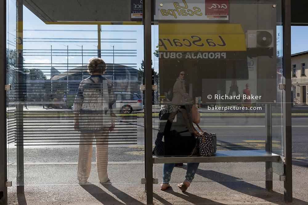 Bus passengers await the next service at a bus stop on Dunajska Cesta (street) in the Slovenian capital, Ljubljana, on 27th June 2018, in Ljubljana, Slovenia.