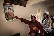 Following an attack on Tawergha, rebel fighters from Misrata comb the streets on a house to house search, tearing down Gadhafi's posters. Rebels pushed into the outskirts of the small town, south east of Misrata, in an attempt to expand their controlled zone around the city and keeping it out of range from deadly Grad rockets. Later in the day, they withdraw out of Tawargha in fear of being encircled by superior forces. 16 May 2011.